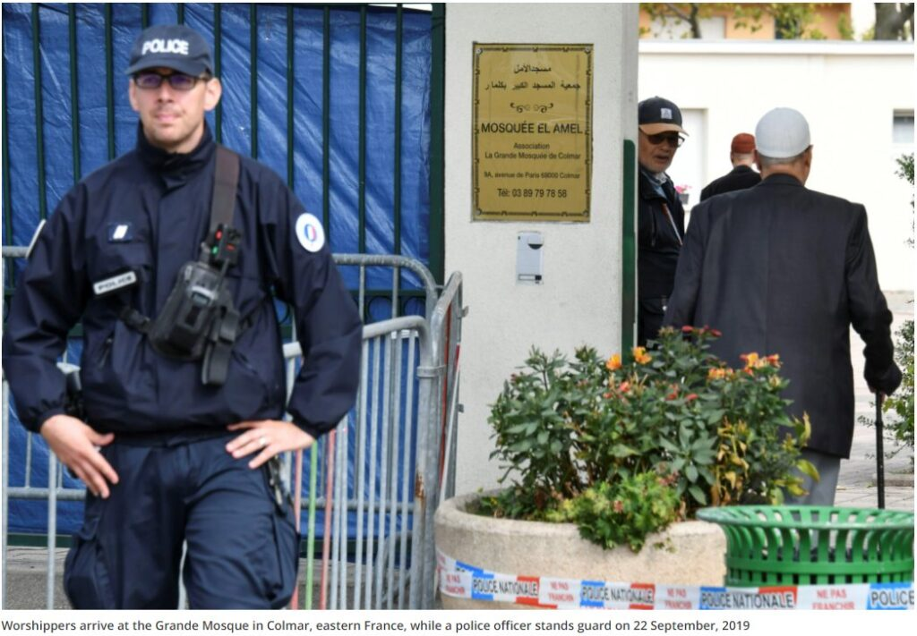 Worshippers arrive at the Grande Mosque in Colmar, eastern France, while a police officer stands guard on 22 September, 2019