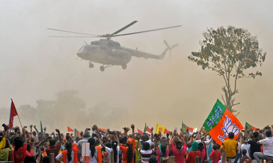 Supporters wave to a helicopter carrying the Indian prime minister, Narendra Modi, at a rally for West Bengal's state legislative assembly elections, at Kawakhali on the outskirts of Siliguri, on 10 April